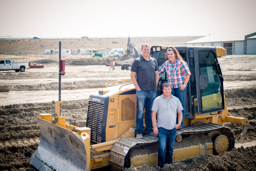 three people standing on construction worksite