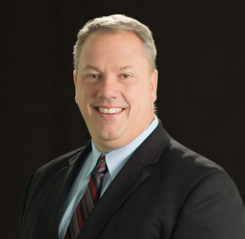 Headshot photo of Eric Pearson, Chief Executive Officer at Community First Bank and HFG Trust in a black blazer with tie.