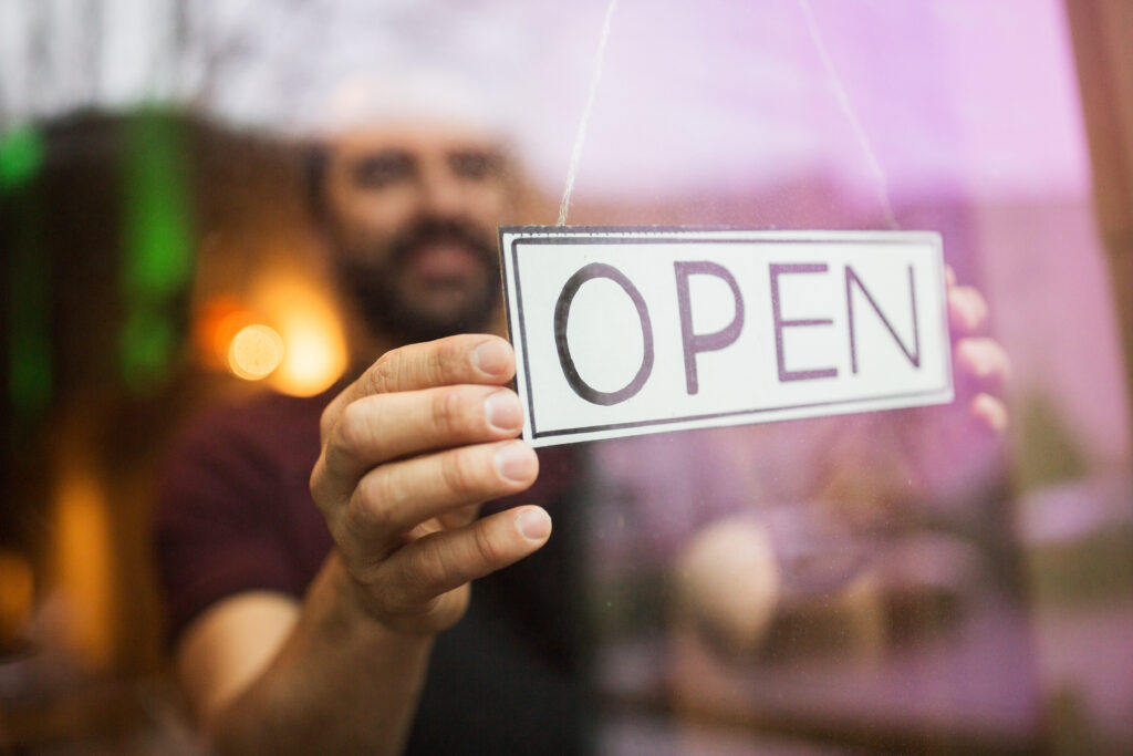 man flipping over open sign at store window