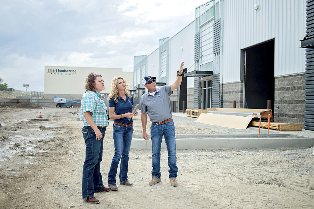 Photo of Amanda Jones, Commercial Lender at Community First Bank outside of construction site with clients looking up and pointing at building.