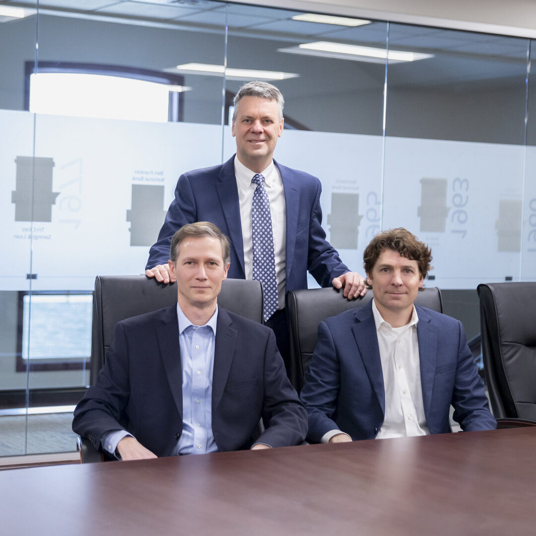Photo of HFG Trust financial advisors (left to right) Paul Hansen, Bob Lagonegro, and Stephen Palm sitting and standing at wooden desk in large conference room.