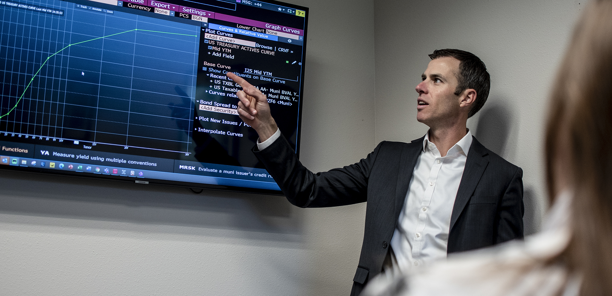 Photo of Anthony Smith, CPA, Portfolio Manager at HFG Trust pointing at financial graph on TV monitor on wall.