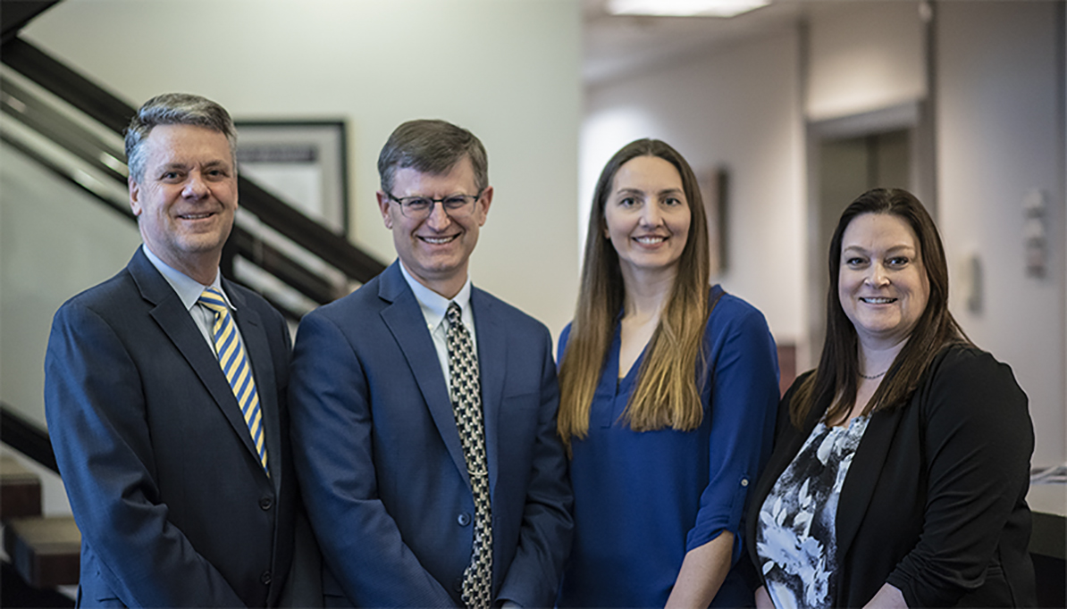 Photo of HFG Trust and Estates team (left to right) Bob Lagonegro, Michael Tallman, Jenny Hubbard, and Allison Smith in front of stairwell.