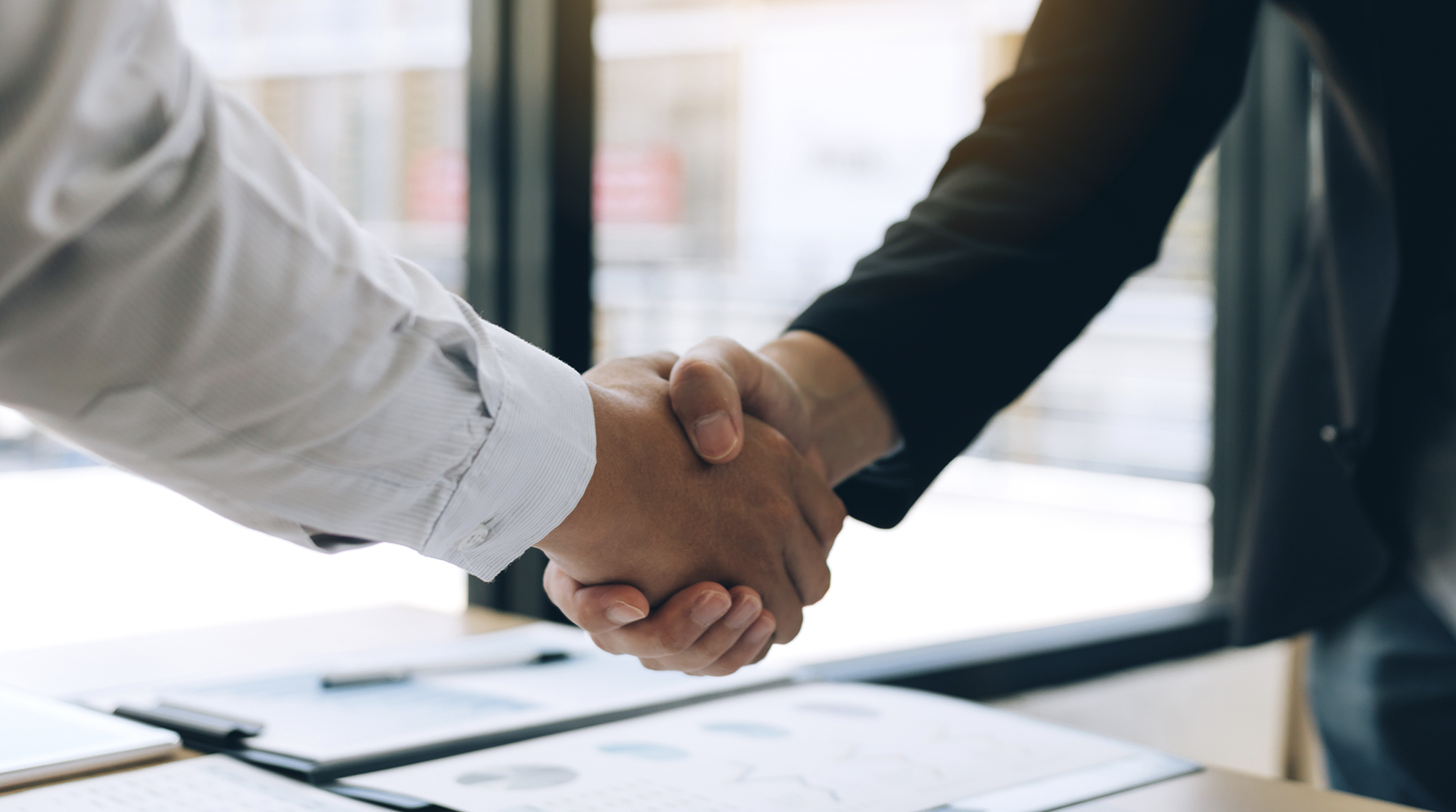 Stock photo of two people shaking hands after a business acquisition has been made.