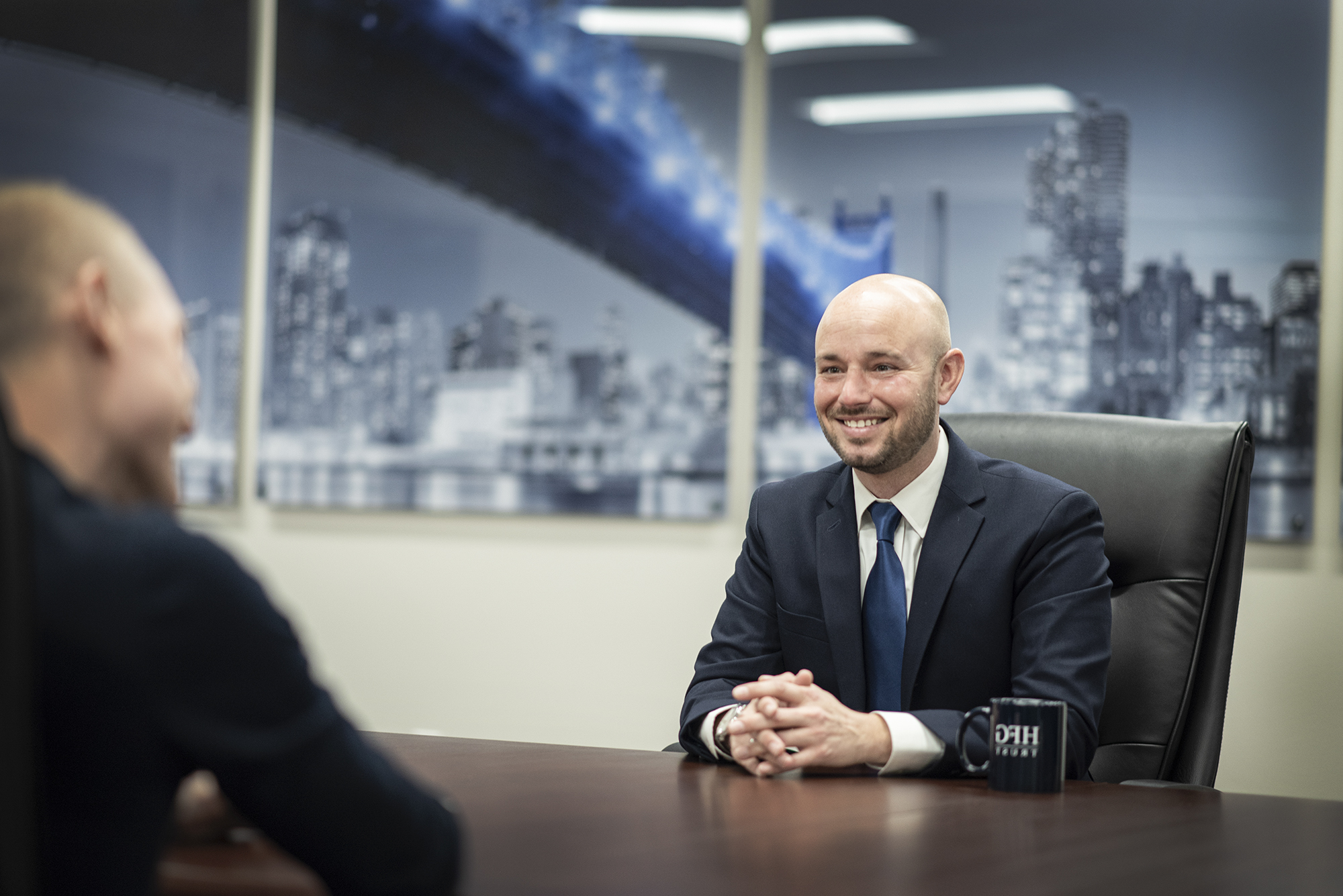 Photo of Private Banker, Andrew Bellon of Community First Bank and HFG Trust meeting with a client at a wooden table in large conference room.