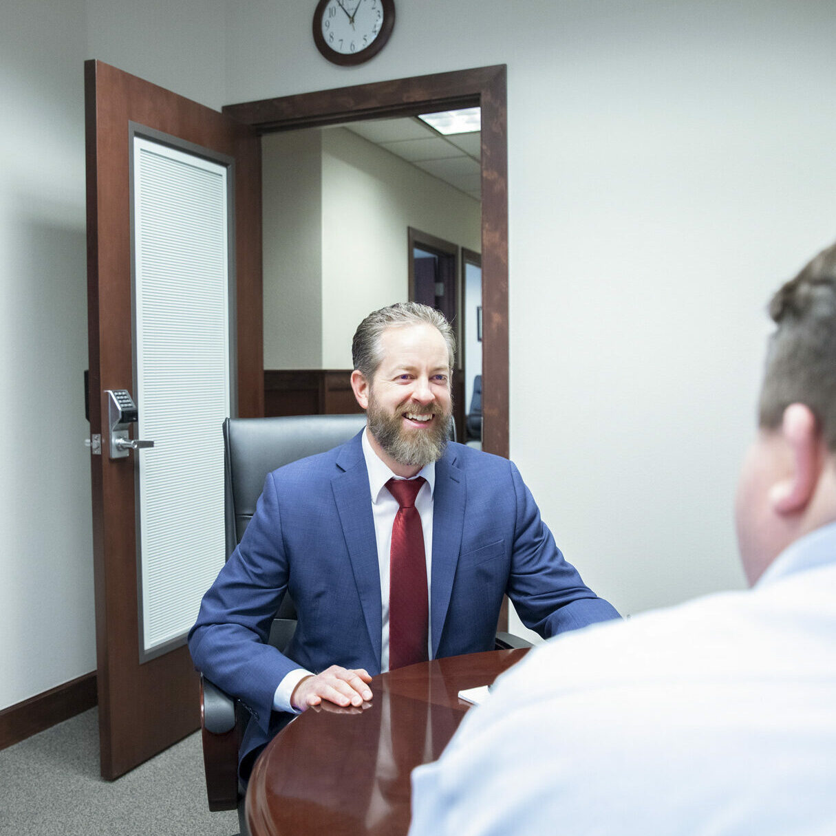 Image of Ben Messinger, CFP, financial advisor at HFG Trust talking with client at wooden table.